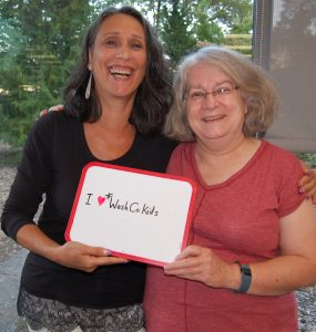 Susan and Maureen hold up sign saying they love Washington County Kids